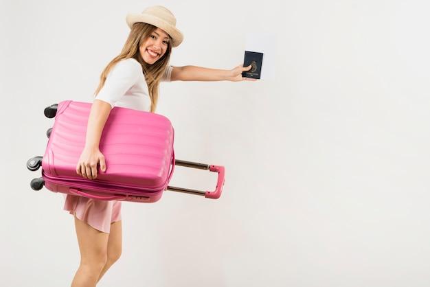 Portret van een vrouwelijke toerist die haar roze bagagezak draagt die paspoort toont tegen witte achtergrond Gratis Foto