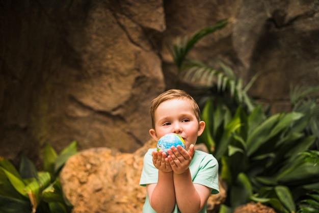 Portret van een wereldbol van de jongen in de hand te houden Gratis Foto