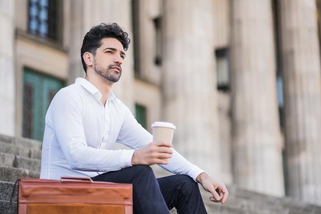 Portret van een zakenman die een kopje koffie drinkt tijdens een pauze van het werk zittend op de trap buiten Gratis Foto