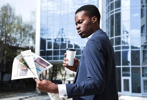 Portret van een zakenman die zich voor de bouw bevindt die beschikbare koffie houdt die de krant leest Gratis Foto