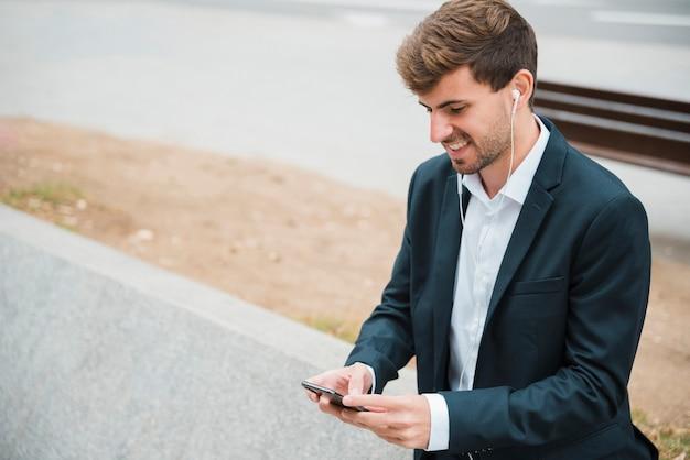 Portret van een zakenman het luisteren muziek op oortelefoon in bijlage op mobiele telefoon Gratis Foto