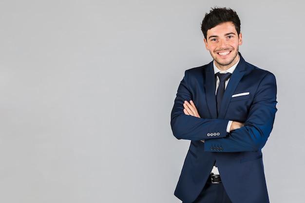 Portret van een zelfverzekerde jonge zakenman met zijn arm gekruist staande tegen een grijze achtergrond Gratis Foto