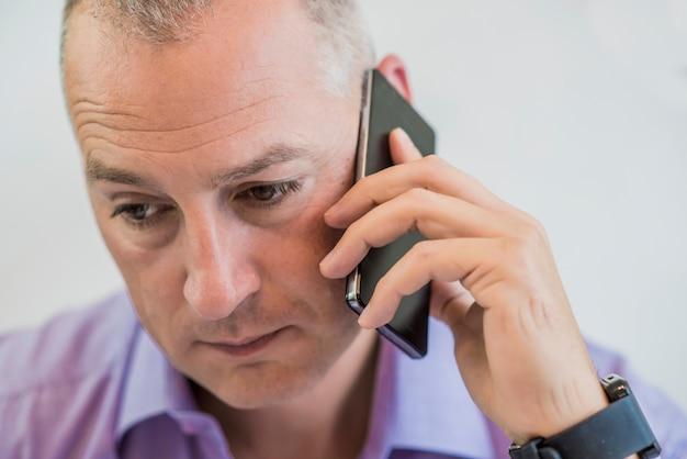 Portret van een zorgige oudere man spreken met slimme telefoon Gratis Foto