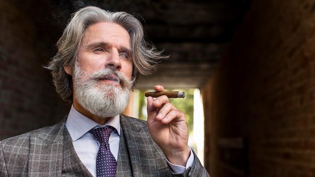 Portret van elegante mannelijke rokende sigaar Gratis Foto