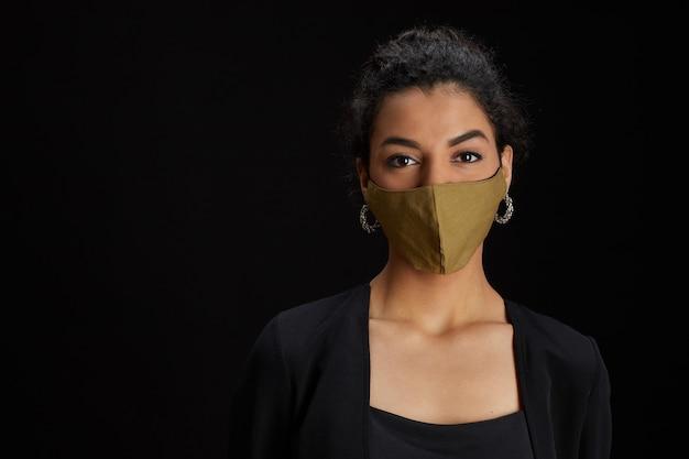 Portret van elegante midden-oosterse vrouw die gezichtsmasker draagt terwijl het poseren tegen zwarte achtergrond op feestje close-up, kopieer ruimte Premium Foto