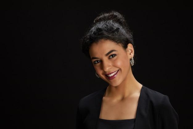 Portret van elegante midden-oosterse vrouw lachend naar de camera terwijl staande tegen een zwarte achtergrond op feestje, kopieer ruimte Premium Foto