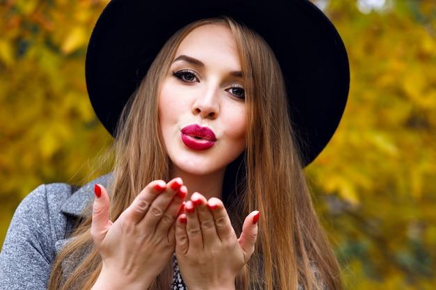 Portret van elegante mooie blonde vrouw poseren op koude herfstdag in het stadspark, het dragen van elegante zwarte hoed, lange haren, lichte make-up close-up. luchtkus verzenden Gratis Foto