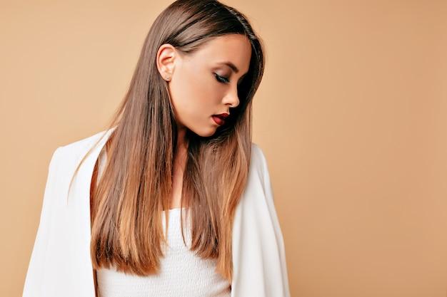 Portret van elegante schattige jonge mooie vrouw, geïsoleerd over beige muur, op zoek profiel, geconcentreerde blik. Gratis Foto