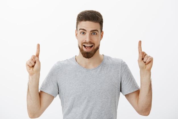 Portret van enthousiaste en opwindende uitgaande donkerbruine man met baard in grijs casual t-shirt handen opsteken en bespreken verbazingwekkende kopie ruimte naar boven poseren tegen witte muur Gratis Foto