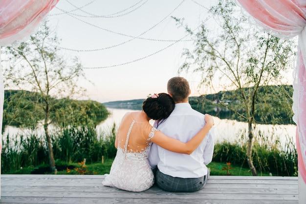 Portret van erachter van bruidspaarzitting op houten plaats en het bekijken meer. Premium Foto
