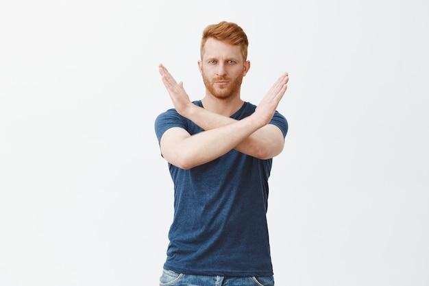 Portret van ernstig ogende volwassen aantrekkelijke roodharige man met borstelharen in blauw t-shirt, kruis met handen maken in de buurt van de borst, stop, genoeg of weigering gebaar tonen Gratis Foto