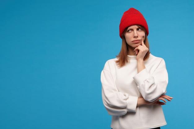Portret van ernstig, volwassen meisje met donkerbruin haar. het dragen van een witte trui en een rode hoed. haar wang aanraken met een vinger en nadenken. kijken naar links op kopie ruimte, geïsoleerd op blauwe muur Gratis Foto