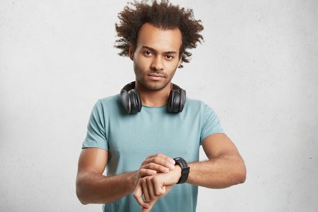 Portret van ernstige donkere man draagt blauwe t-shirt, luistert tracks met koptelefoon Gratis Foto