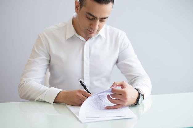 Portret van ernstige jonge zakenman die vragenlijst invullen Gratis Foto