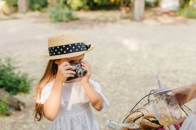 Portret van ernstige kind met camera draagt trendy schipperhoed versierd met zwart lint. meisje met bruin haar dat foto van picknickmand neemt die haar moeder houdt. Gratis Foto