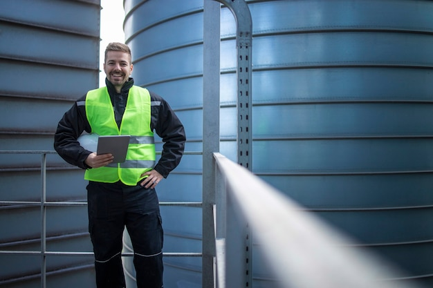 Portret van fabrieksingenieur werknemer permanent op metalen platform tussen industriële opslagtanks en kijken naar de camera Gratis Foto