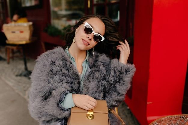 Portret van fabuleuze jonge vrouw met donker haar, geklede bontjas en zonnebril Gratis Foto