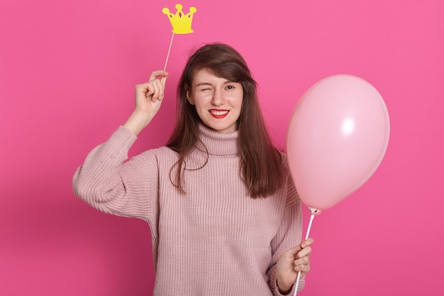 Portret van flirterige aantrekkelijke donkerharige knipogende vrouw met roze ballon Premium Foto
