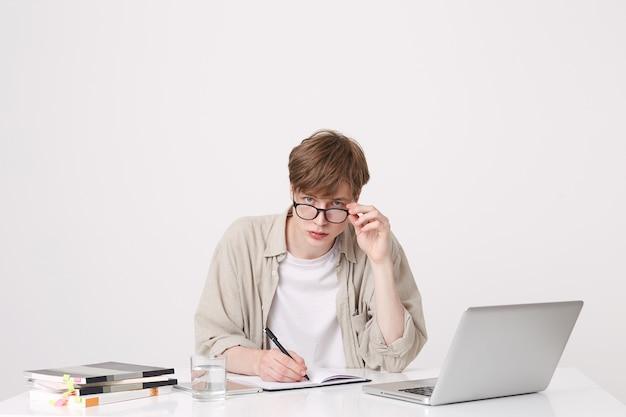 Portret van geconcentreerde jongeman student draagt een bril en beige overhemd schrijven en studeren aan de tafel met laptop en notebooks geïsoleerd over witte muur Gratis Foto
