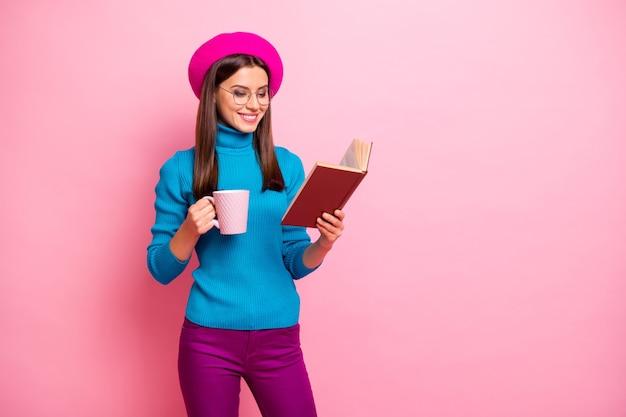 Portret van gefocust vrolijk meisje hebben weekends gelezen leerboek houden warme drank mok draag paarse broek. Premium Foto