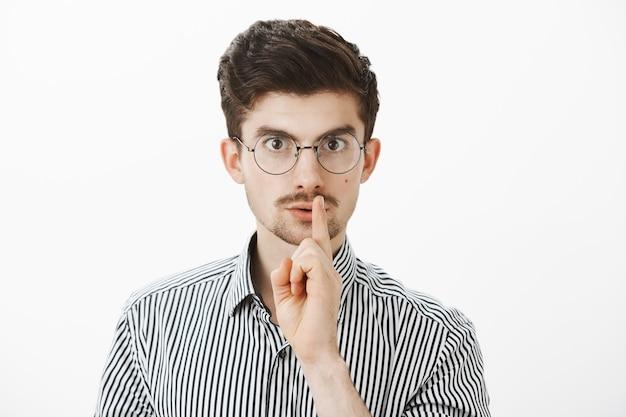 Portret van gefocuste serieuze nerdy kerel in ronde bril, shh zegt terwijl hij een zwijggebaar maakt met wijsvinger voor de mond, nerveuze vriend voelt geheim zal vertellen Gratis Foto