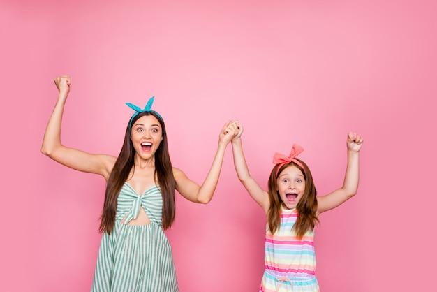Portret van geïmponeerde meisjes die hun vuisten opheffen, handen schreeuwen wow omg het dragen van hoofdbanden levensstijl rok jurk geïsoleerd op roze achtergrond Premium Foto