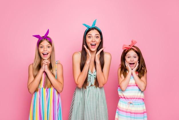 Portret van geïmponeerde meisjes die hun wangen aanraken die schreeuwend nieuws horen die een lichte rok dragen die over roze achtergrond wordt geïsoleerd Premium Foto
