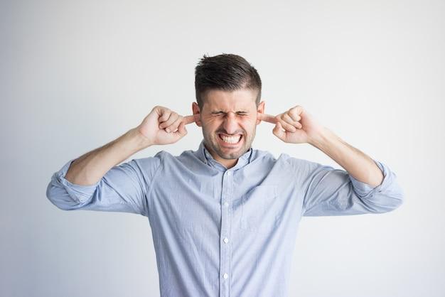 Portret van geïrriteerde jonge mens die oren met vingers stopt. Gratis Foto