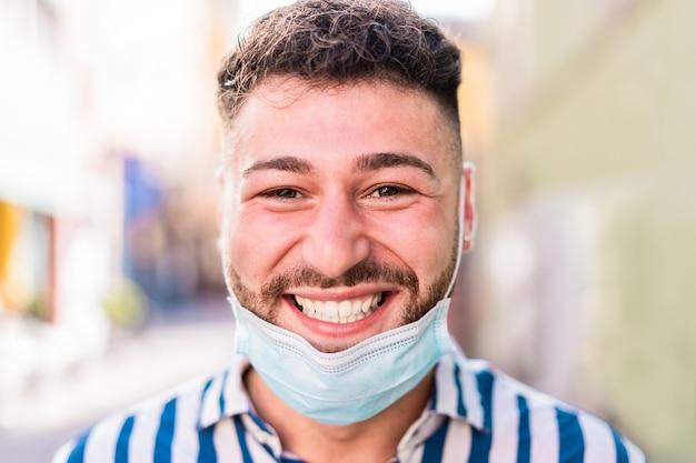 Portret van gelukkig blanke man die lacht voor camera terwijl het dragen van medische beschermend masker Premium Foto
