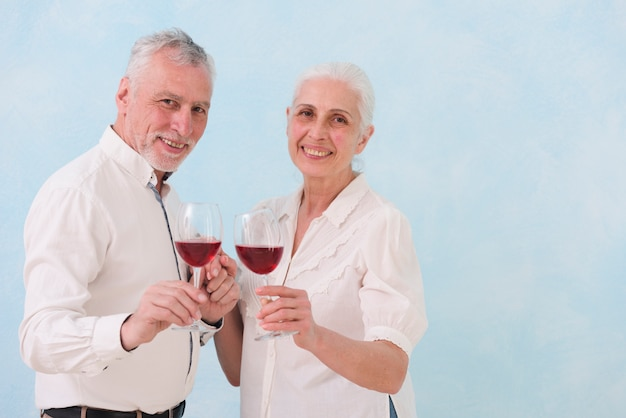 Portret van gelukkig echtgenoot en vrouwenholding wijnglas die camera bekijken Gratis Foto