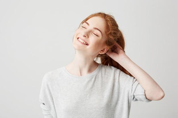 Portret van gelukkig jong leuk roodharigemeisje die met gesloten ogen glimlachen wat betreft haar. Gratis Foto