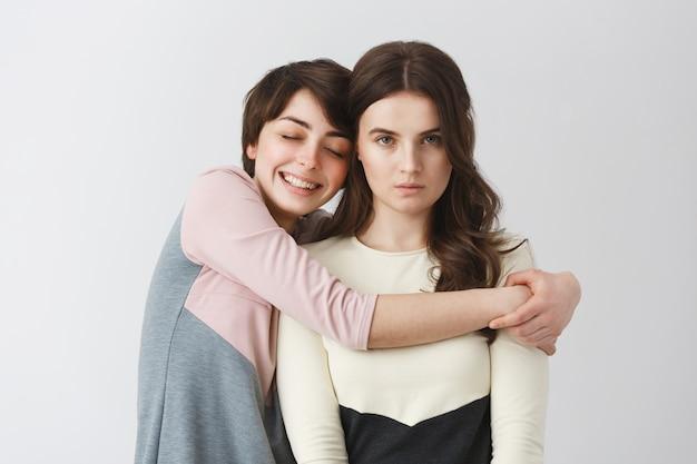Portret van gelukkig lesbisch meisje met kort haar knuffelen haar knorrige vriendin voor foto op universiteitsfeest. liefde en relatie. Gratis Foto