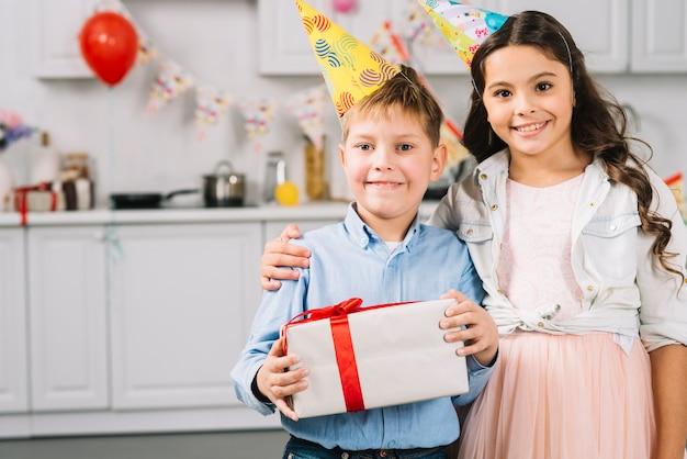 Portret van gelukkig meisje met de verjaardagscadeau van de jongensholding Gratis Foto