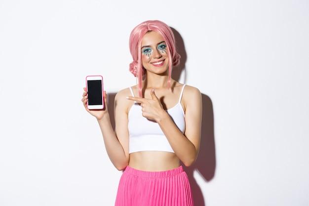 Portret van gelukkig mooi vrouwelijk model in roze glamourpruik en lichte make-up, wijzende vinger op gsm-scherm, toepassing of banner tonen. Gratis Foto