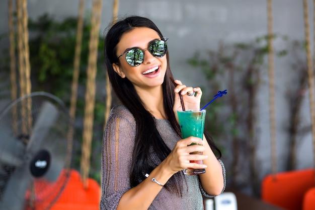 Portret van gelukkig mooie brunette vrouw drinken lekkere koude cocktail, stijlvolle outfit en gespiegelde zonnebril close-up, geniet van haar weekend, feest. Gratis Foto