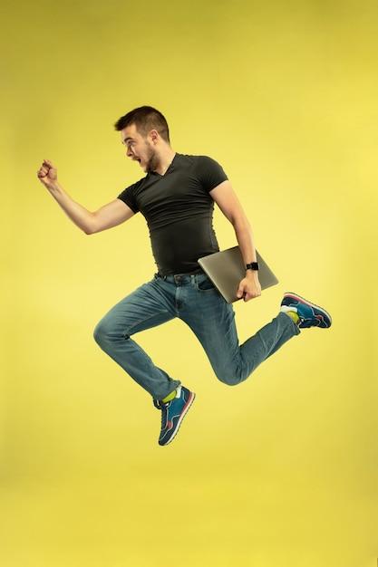 Portret van gelukkig springende man met gadgets geïsoleerd op geel Gratis Foto