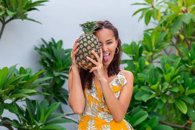 Portret van gelukkige aziatische glimlachende vrouw in gele de greepananas van de de zomerkleding Gratis Foto