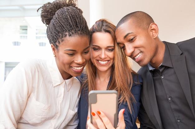 Portret van gelukkige bedrijfscollega's die mobiele telefoon met behulp van Gratis Foto