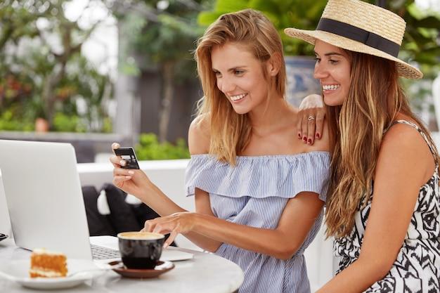 Portret van gelukkige beste vriendinnen betalen met creditcard, banktoepassing gebruiken op moderne laptopcomputer, bestellingen plaatsen, aromatische koffie drinken met fluitje van een cent. online aankoopconcept. Gratis Foto
