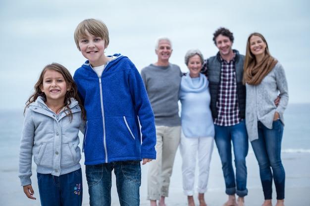 Portret van gelukkige broers en zussen terwijl familie op achtergrond Premium Foto