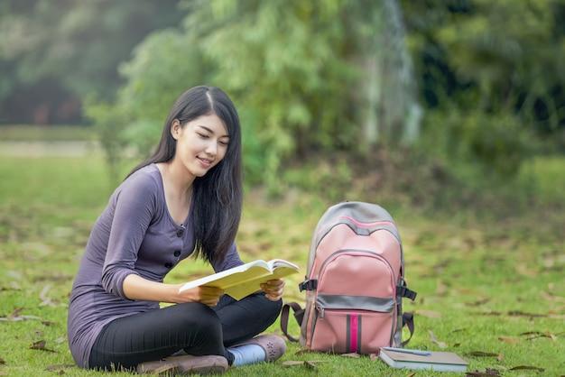 Portret van gelukkige charmante aziatische vrouw die een boek in openlucht leest Premium Foto
