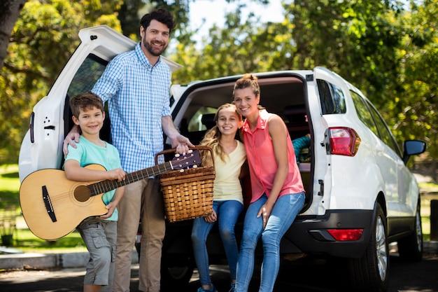 Portret van gelukkige familie in de buurt van auto Premium Foto