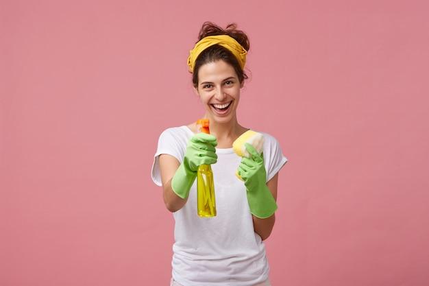 Portret van gelukkige glimlachende meid in wit opgeruimd t-shirt en groene beschermende handschoenen die haar wasmiddel en spons vóór het werk aantonen. mensen, huishoudelijk werk, huishouden en schoonmaakconcept Gratis Foto