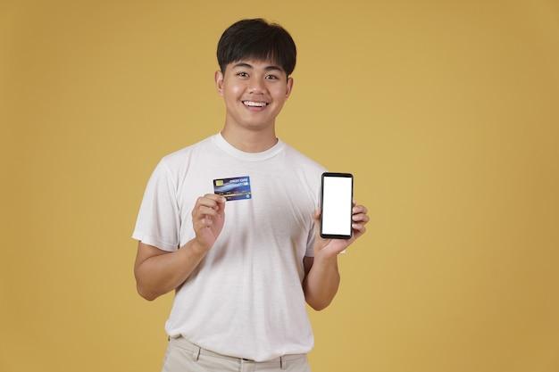Portret van gelukkige jonge aziatische man gekleed terloops met smartphone en creditcard om online te winkelen geïsoleerd Premium Foto