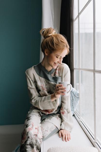 Portret van gelukkige jonge blonde uitgaven ochtend kijken door groot raam met kopje koffie of thee, thuis blijven. turquoise muur. zijden pyjama's in bloemen dragen, haar omhoog. Gratis Foto