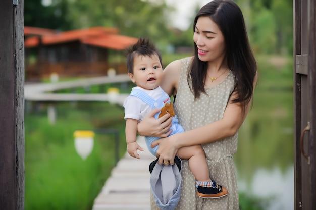 Portret van gelukkige jonge moeder met kleine schattige babyjongen tijd samen doorbrengen in zomer park. Premium Foto