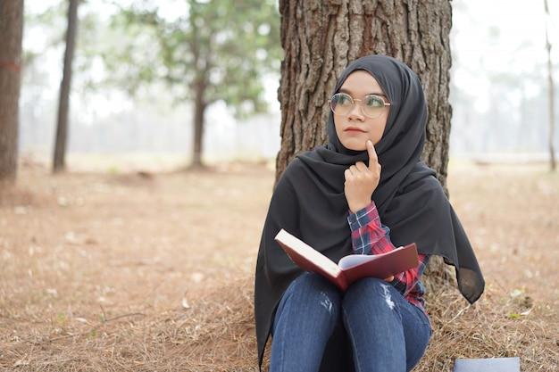 Portret van gelukkige jonge moslimvrouw zwarte hijab en schots overhemd die een boek op de achtergrond van het de herfstseizoen lezen. Premium Foto