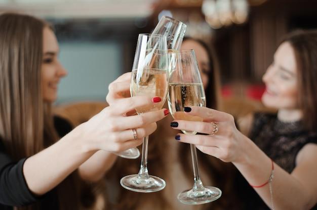 Portret van gelukkige jonge vrienden aanraken van de bril met elkaar. Premium Foto