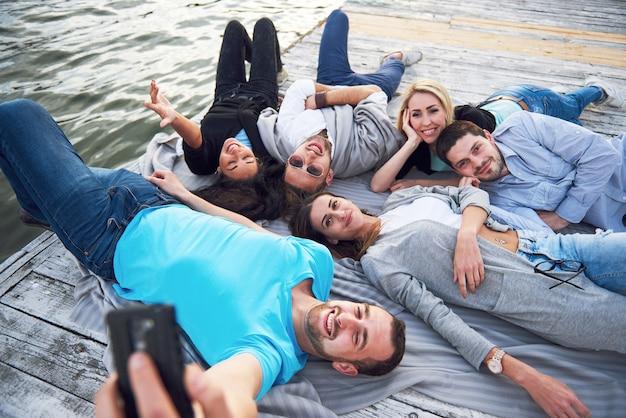 Portret van gelukkige jonge vrienden op de pier aan het meer. terwijl je geniet van de dag en selfie maakt. Gratis Foto