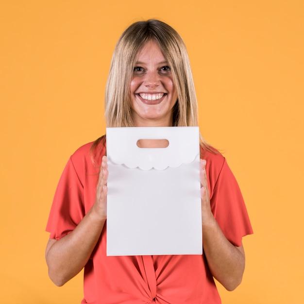 Portret van gelukkige jonge vrouw die witboekzak houdt Gratis Foto